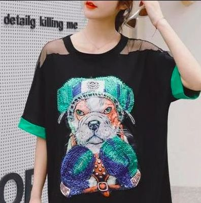 Image of a girl wearing an english bulldog boxer with green gloves themed sew on patch on a black shirt.