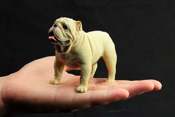 Image of a man holding in his palm a small figurine in the shape of a standing english bulldog