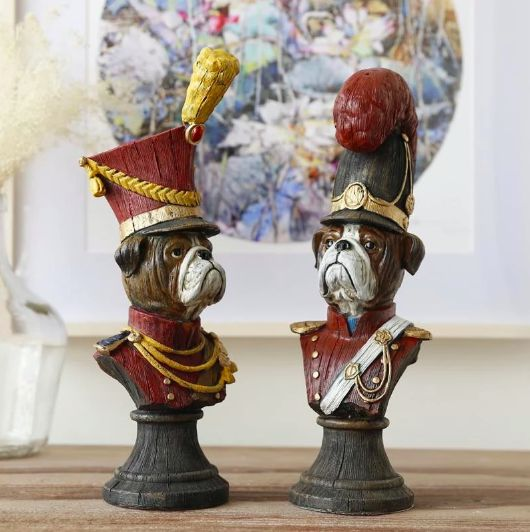 Image of two decorative sculptures in the shape of English Bulldogs dressed up in 19th century military outfits
