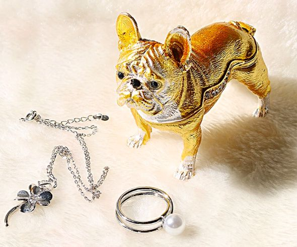 Image of a jewellery box in the shape of a golden french bulldog on a white surface with a ring and bracelet lying outside