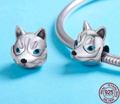 Image of two silver bracelet or necklace charm beads in the shape of a Siberian Husky face on a table with a blue background