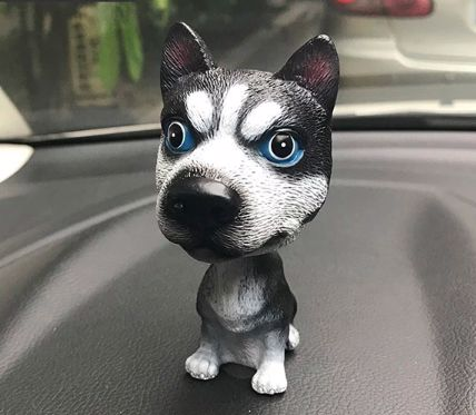 Image of a car bobble head in the shape of a Siberian Husky on a car's dashboard