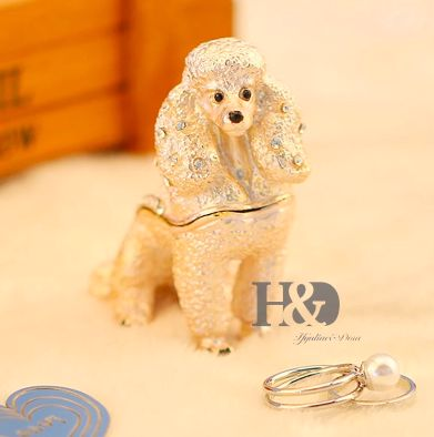 Image of a small jewellery box in the shape of a standing Poodle on a table with a ring lying outside