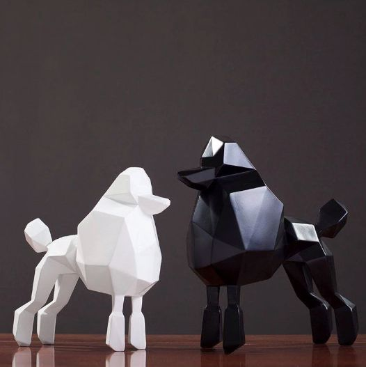 Image of two statues, one black and one white, both shaped like abstract standing Poodle dogs