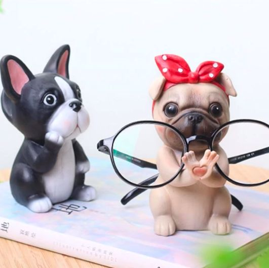 Image of two desktop glasses holders, one is a gift pug with a red bandana holding a pair of spectacles with another which looks like a Boston Terrier on the side