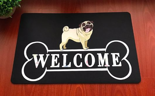 Image of a black welcome doormat with a photo of a Pug standing on top of a bone with the text Welcome