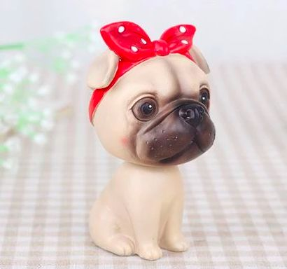 Image of a bobble head for car which looks like a cute she pug wearing a red bandana