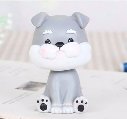 Image of a Schnauzer car bobble head on a tabletop