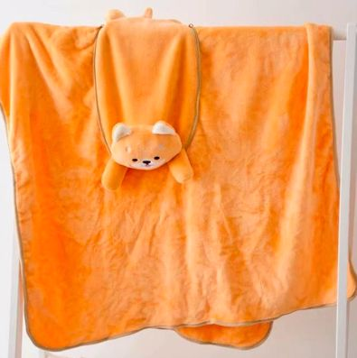 Image of an orange blanket hung out of a blanket hanger to better showcase the Shiba Inu design