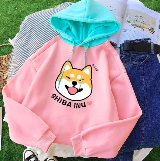Image of a pink sweatshirt with a teal hood and a cute smiling Shiba Inu design
