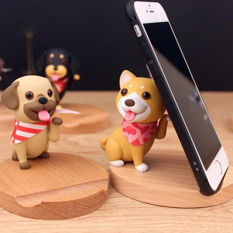 Image of a mobile phone holder on a wooden platform holding a phone with a orange Shiba Inu design