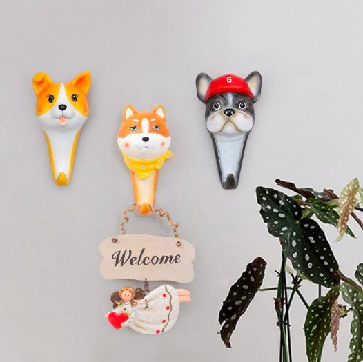 Image of three wall hooks on a wall, one of them which looks like a Shiba Inu