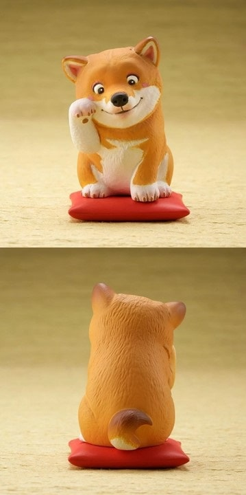 Image of a cute desktop ornament one below the other, front and back view which looks like a Shiba Inu sitting on a red cushion pillow waving with one arm up