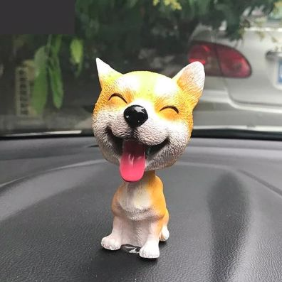 Image of a bobble head on a car dashboard in the shape of a sitting orange Shiba Inu with tongue out smiling with eyes closed