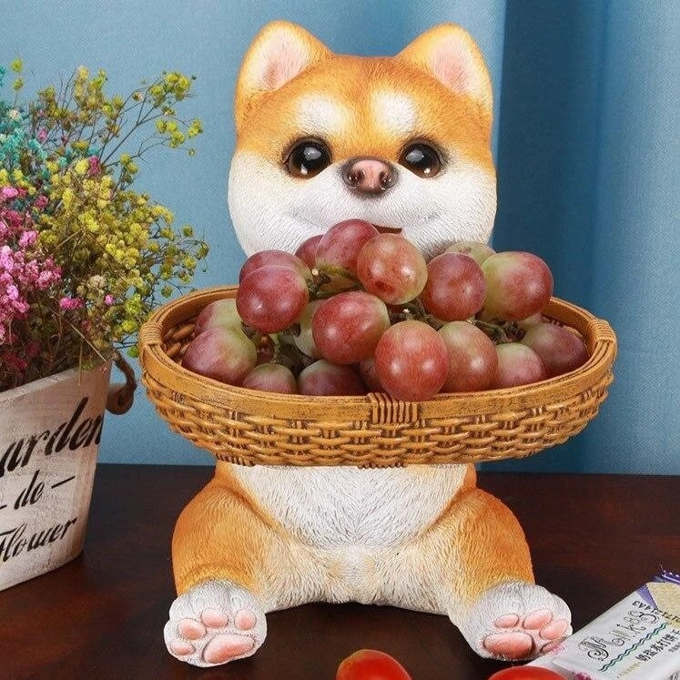 Image of Shiba Inu Statue made of resin sitting on a table and holding basket with full of apples
