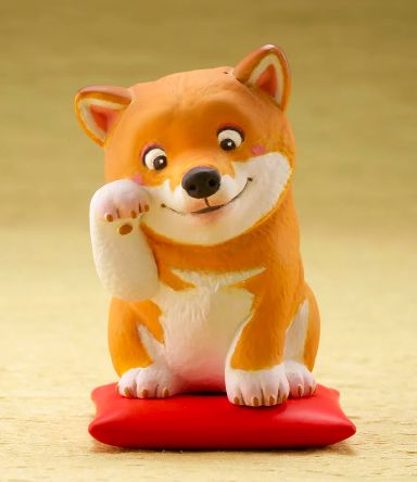 Image of a desktop ornament in the shape of a Shiba Inu dog sitting on a red cushion pillow