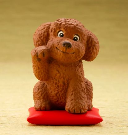 Image of a super cute desktop ornament in the shape of a waving Toy Poodle or Cockapoo sitting on a red cushion pillow