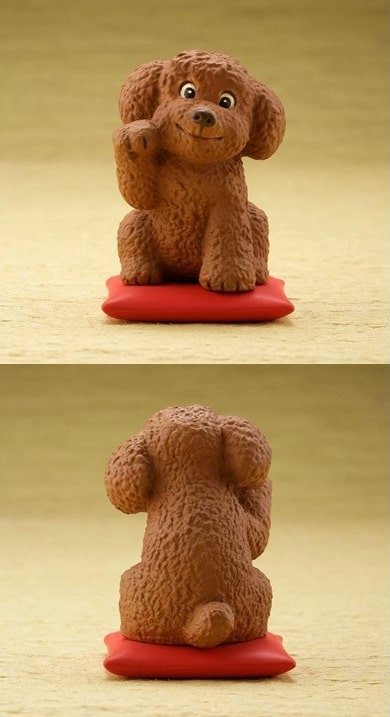 Image of a cute desktop ornament one below the other, front and back view which looks like a Toy Poodle / Cockapoo sitting on a red cushion pillow waving with one arm up
