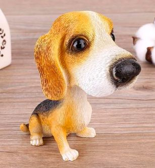 Image of a car bobble head in the shape of a sitting beagle on a wooden table