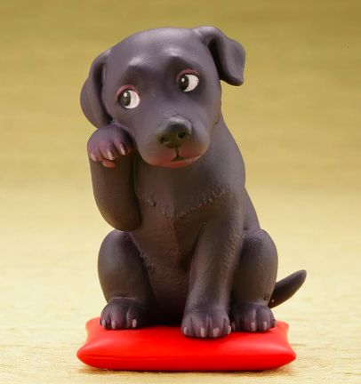 Image of a cute desktop ornament which looks like a black labrador sitting on a red cushion pillow waving with one arm up