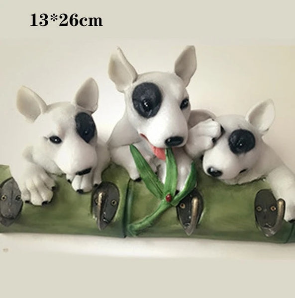 Image of three bull terriers handing on a wall hook