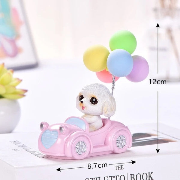 Image of a Bichon Frise car bobblehead made of resin in which bichon frise is sitting in a car with balloons design