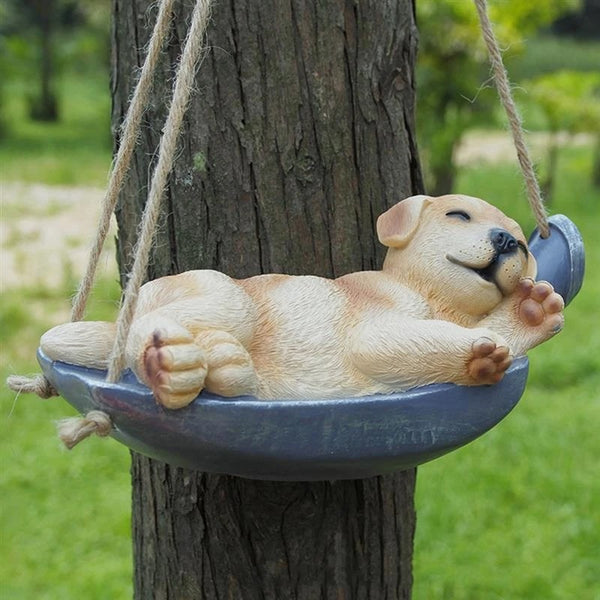 Image of a Labrador Sleeping Statue hanging on a tree branch made of resin