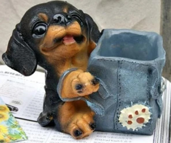 Image of a pen or pencil holder in the shape of a Dachshund dog wearing a blue backpack