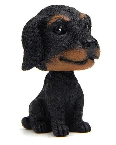 Image of a miniature bobblehead accessory in the shape of a dachshund, made of resin