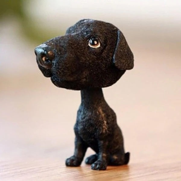 Image of a bobble head accessory in the shape of a black labrador made of resin