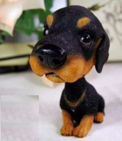 Image of a bobble head accessory in the shape of a dachshund, made of resin