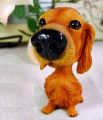 Image of a bobble head accessory in the shape of a golden retriever made of resin