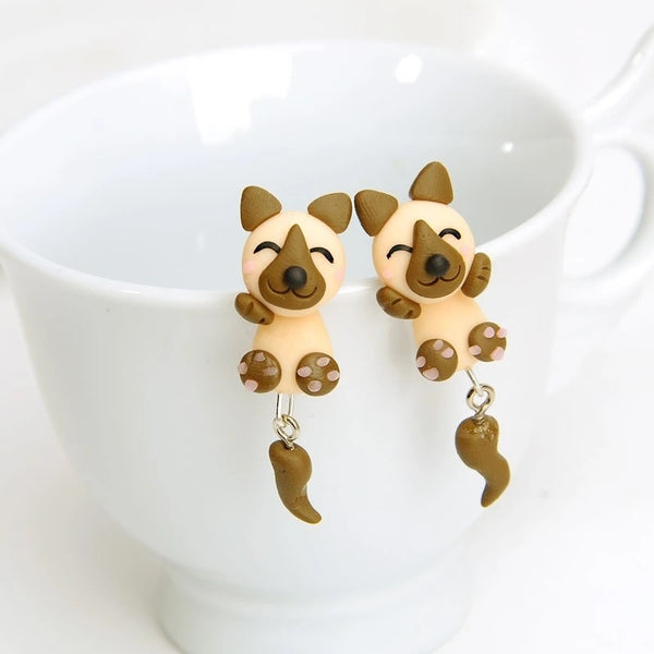 Image of two adorable earrings hanging in the cup in the shape of german shepherd handmade with polymer clay