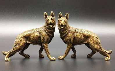 Two small identical german shepherd statues standing side by side on a table