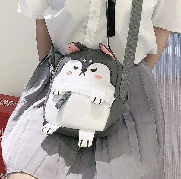 Image of a gray color messenger bag in the shape of a husky, holding by a girl