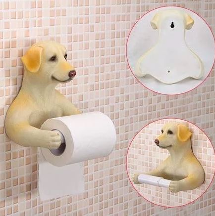 Image of a toilet roll holder on a bathroom wall in the shape of a yellow labrador retriever with arms stretching out holding the toilet paper