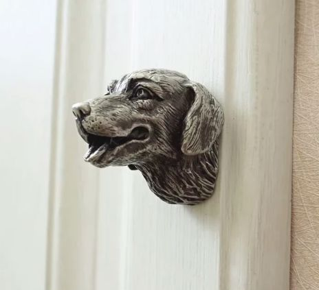 Image of a silver drawer pull door handle on a white door in the shape of a smiling Labrador retriever's face