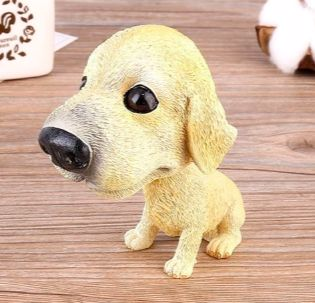 Image of a car bobble head on a wooden table in the shape of a sitting yellow Labrador retriever