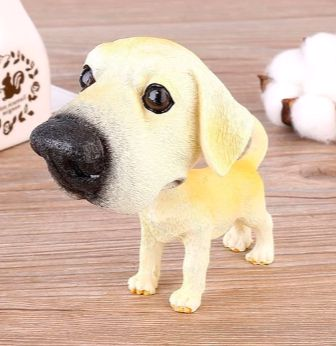 Image of a car bobble head on a wooden table in the shape of a standing yellow Labrador retriever