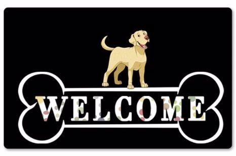 Image of a black rubber doormat with a Labrador standing on top a giant bone which says Welcome