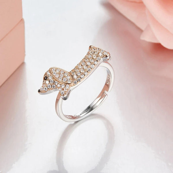 Image of a studded ring in the shape of a dachshund, made of pure 925 sterling silver with zircon stone detailing