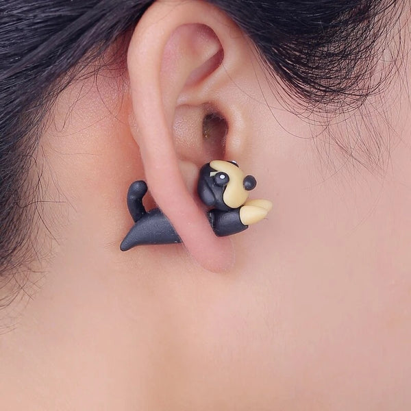 Image of an adorable earring in the shape of a dachshund wore by a girl, handmade with polymer clay