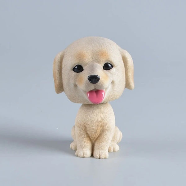 Image of a car bobble head in the shape of a smiling yellow Labrador retriever
