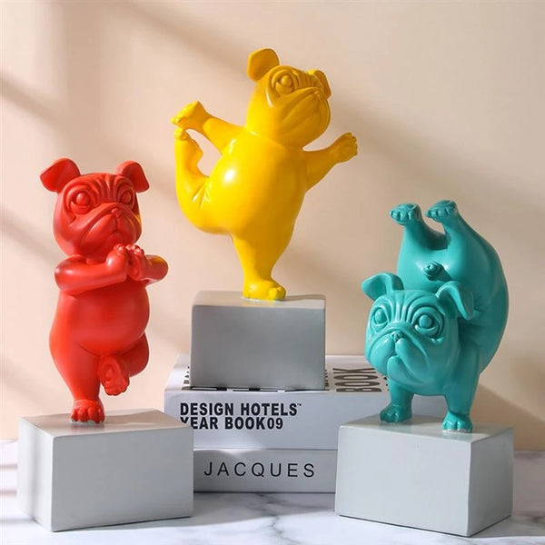 Image of three Pug statues doing yoga in yellow, teal and red color, made of resin