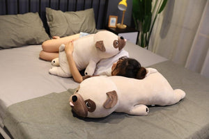 Image of a girl on the bed sleeping with two Pug stuffed animals soft plush toys