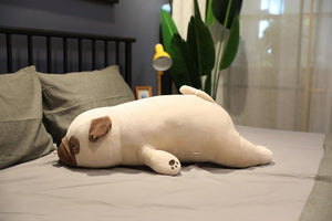 Image of a Pug stuffed animal lying on the bed