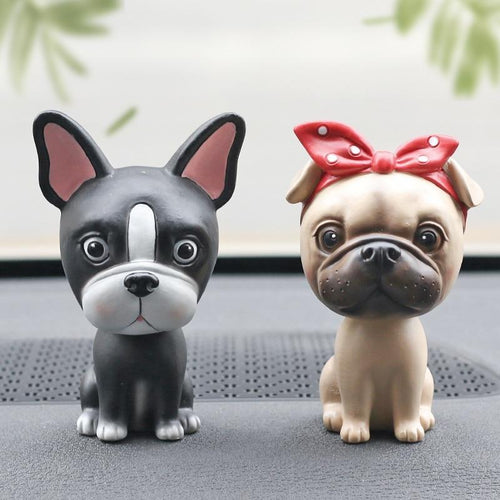 Image of two nodding bobbleheads on a car dashboard shaped like a Boston Terrier and a girl Pug