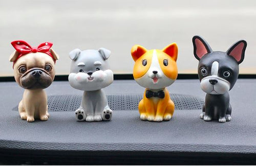 Image of four nodding bobbleheads on a car dashboard shaped like a girl Pug, Miniature Schnauzer, Corgi, and Boston Terrier