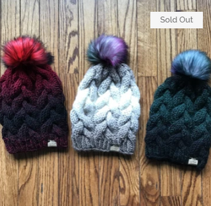 hand knit cabled hats (black & red, tan & taupe, green & black), with fluffy poms