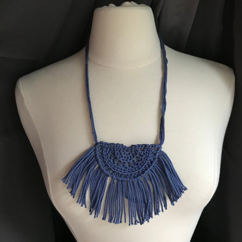 Necklace made of yarn being worn by model form figure.  Necklace color is a jewel tone Blue called Denim.  Necklace design is half circle made with textured stitches and fringe hanging from the edge around.